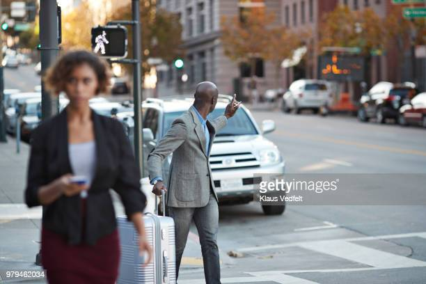 Businessman with rolling suitcase hailing cab on the streets of San Francisco
