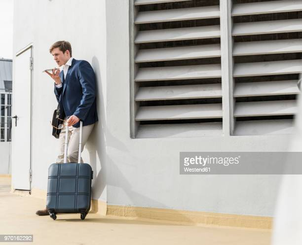 Businessman with rolling suitcase using smartphone at parking garage