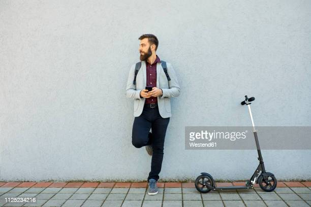 businessman with scooter and cell phone leaning against a wall - leaning stock pictures, royalty-free photos & images
