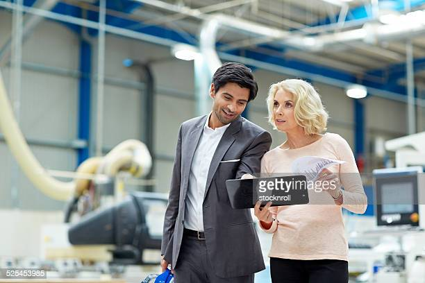 Businessman with senior woman at factory shop floor