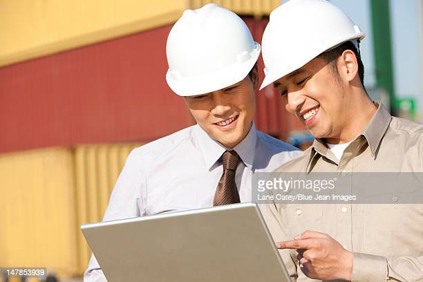 businessman with shipping industry worker looking over a laptop