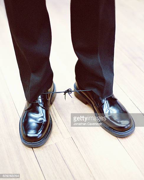 Businessman with Shoelaces Tied Together