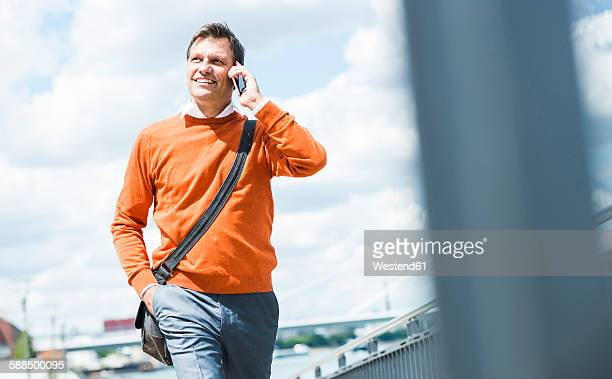 Businessman with shoulder bag walking while talking on the phone