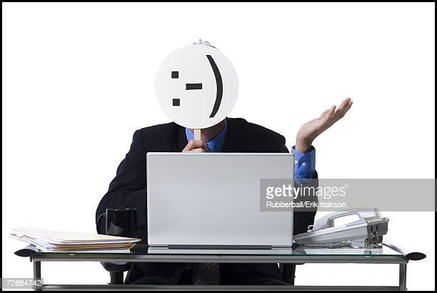 Businessman with sideways happy mask and laptop
