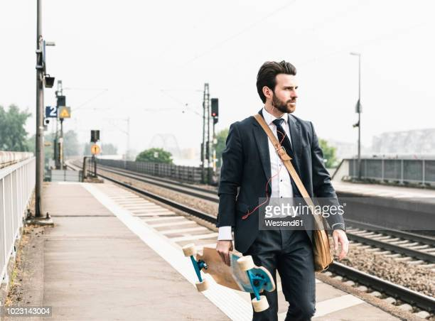 businessman with skateboard and earphones walking at the platform - 斜め掛けバッグ ストックフォトと画像
