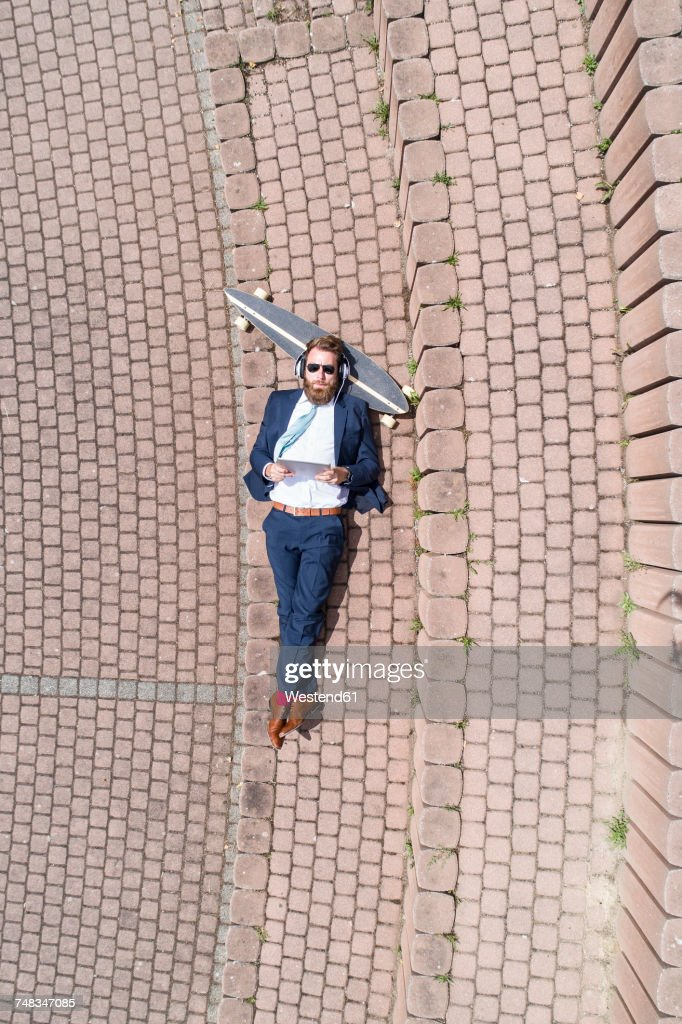 Businessman with skateboard lying on a wall using tablet and headphones : Photo