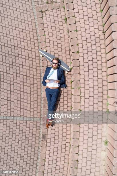 Businessman with skateboard lying on a wall using tablet and headphones