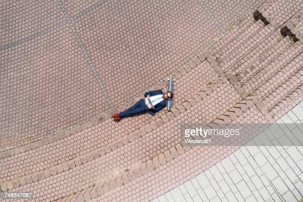 businessman with skateboard lying on a wall using tablet and headphones - schrägansicht stock-fotos und bilder