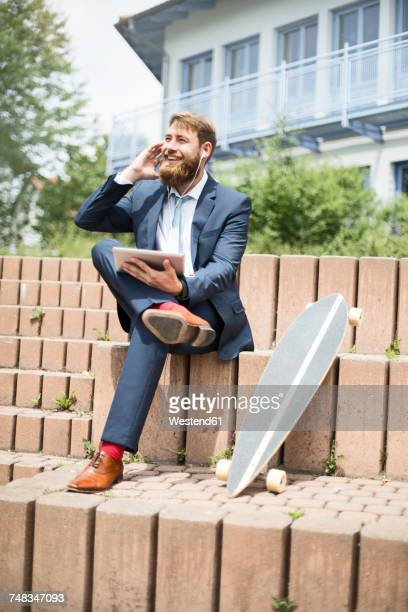 Businessman with skateboard, tablet and earphones on the phone