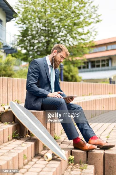 Businessman with skateboard using tablet and earphones