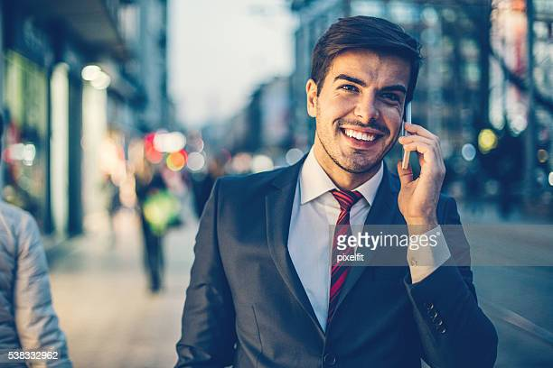 Businessman with smart phone and street lights