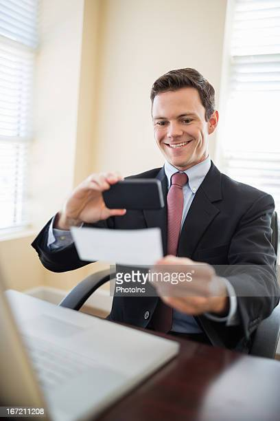 Businessman With Smart Phone Paying Check