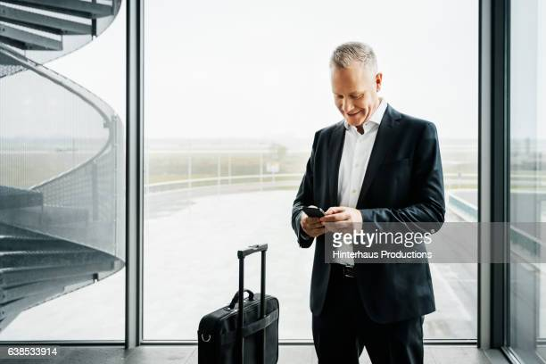 Businessman with smart phone standing at airport