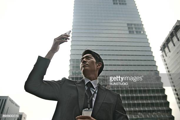 Businessman with smart phone standing in city