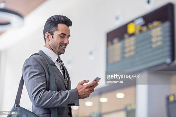 Businessman with smartphone at timetable at the airport