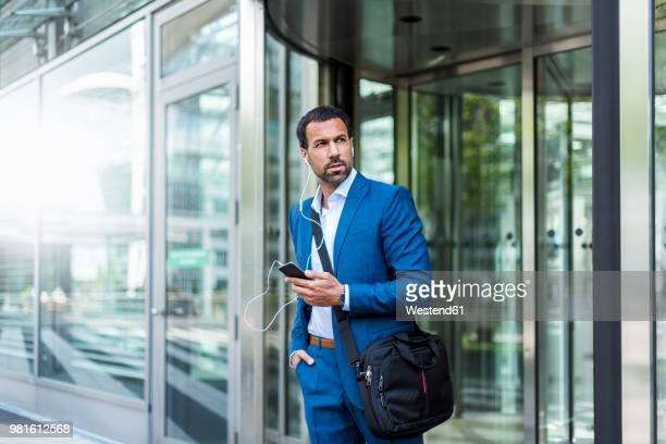 Businessman with smartphone, earphones and laptop bag