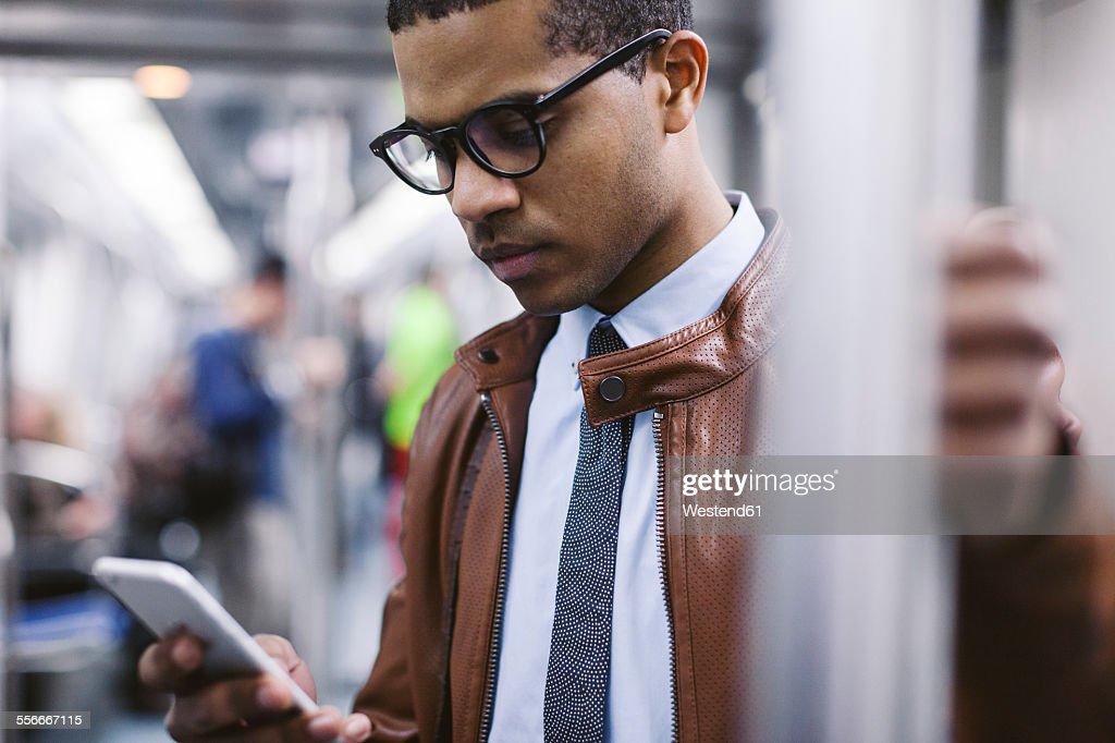 Businessman with smartphone on the subway train : ストックフォト