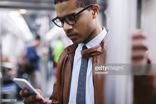 Businessman with smartphone on the subway train
