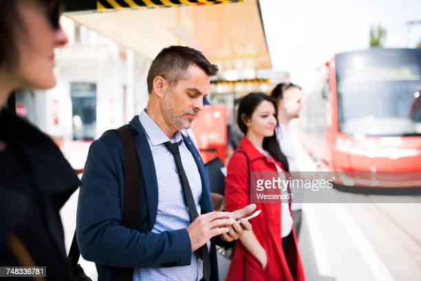 businessman with smartphone waiting at the bus stop - esperar - fotografias e filmes do acervo