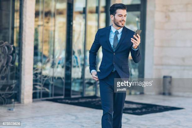 Businessman with smartphone walking out of the building