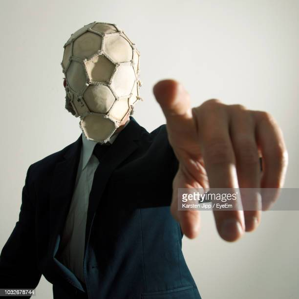 businessman with soccer ball covering face pointing against white background - face guard sport stock pictures, royalty-free photos & images