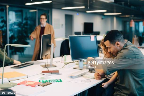 Businessman with son sitting at desk in creative office