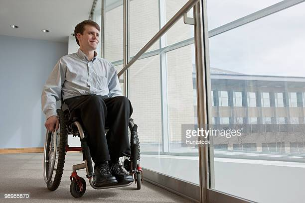 Businessman with spinal cord injury in a wheelchair in an office building