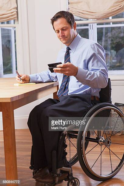 businessman with spinal cord injury in a wheelchair using a smartphone - quadriplegic stock photos and pictures