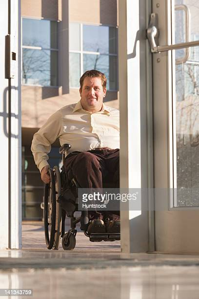 Businessman with spinal cord injury in wheelchair using automatic door entrance in office building