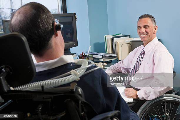 businessman with spinal cord injury talking to his colleague on a ventilator and with duchenne muscular dystrophy - duchenne muscular dystrophy stock photos and pictures