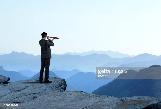 businessman with spyglass looking out toward mountain range - la via giusta foto e immagini stock