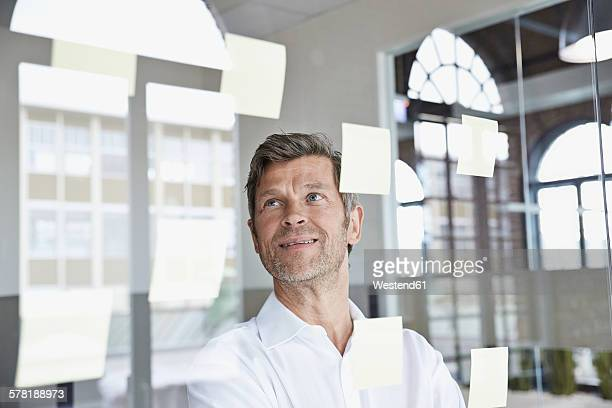 businessman with sticky notes on glass pane in office - variable schärfentiefe stock-fotos und bilder