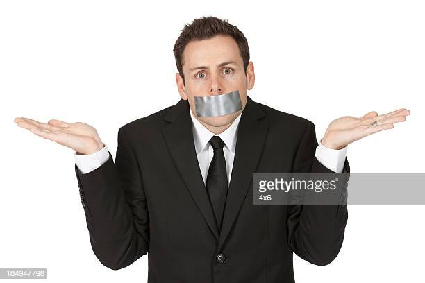 Businessman with sticky tape on his mouth