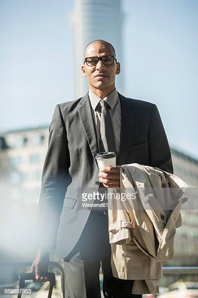 Businessman with suitcase and coffee to go