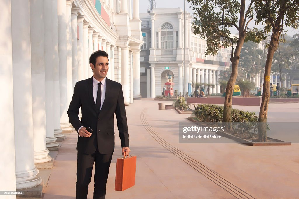 Businessman with suitcase and mobile phone , INDIA , DELHI : Stock Photo