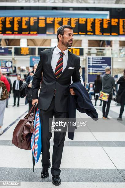 Businessman with suitcase and overcoat near the arrival departure board