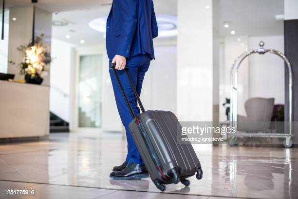businessman with suitcase approaching reception at luxury hotel - approaching stock pictures, royalty-free photos & images