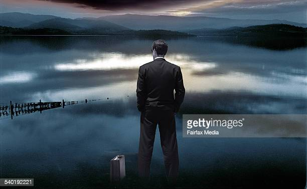 Businessman with suitcase by a lake