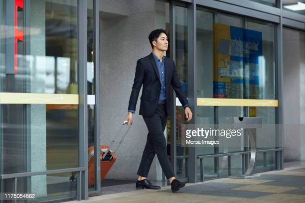 businessman with suitcase leaving airport - blazer jacket stock pictures, royalty-free photos & images