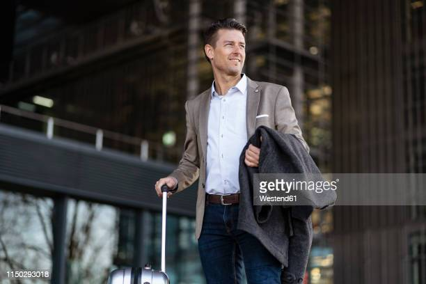 businessman with suitcase standing outdoors - upper class stock pictures, royalty-free photos & images