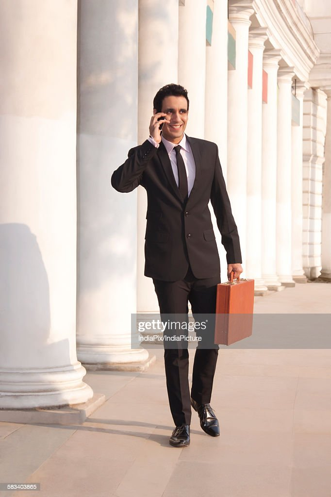 Businessman with suitcase talking on a mobile phone  , INDIA , DELHI : Stock Photo