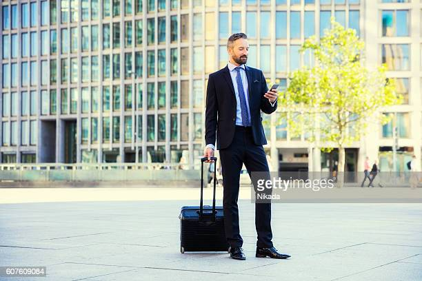 businessman with suitcase using phone while standing against buildings - 可動性 ストックフォトと画像