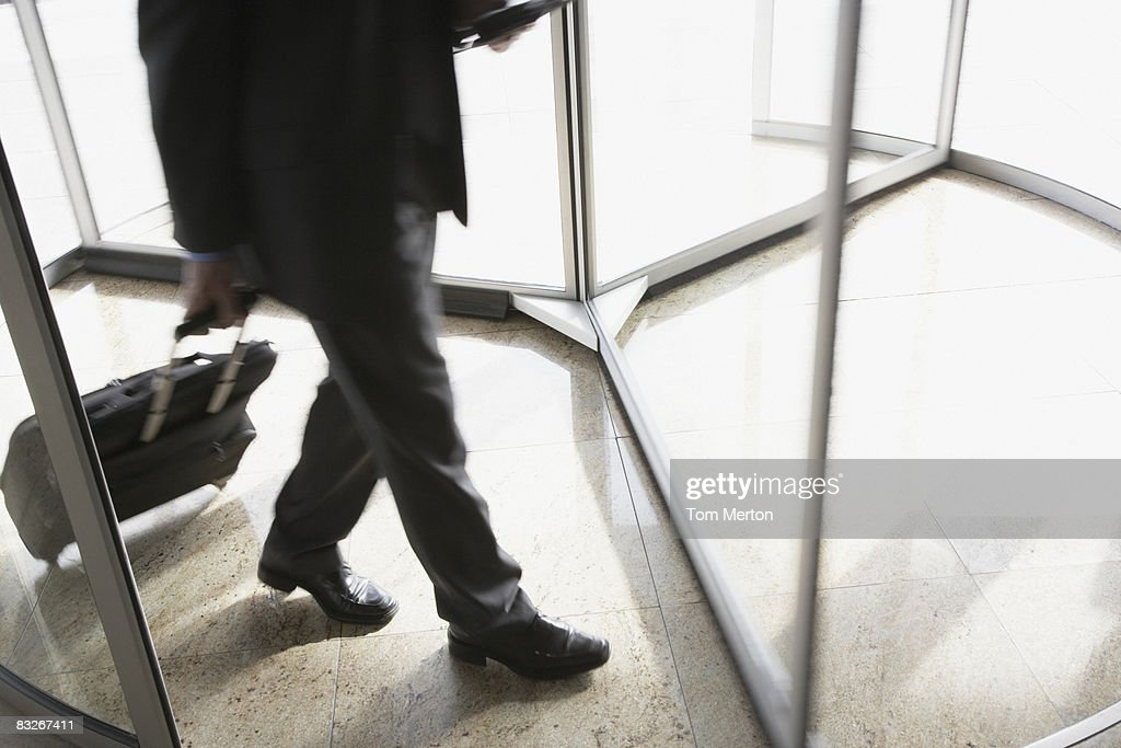 Businessman with suitcase using revolving door : Stock Photo