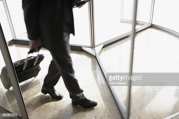 businessman with suitcase using revolving door - revolve stock photos and pictures