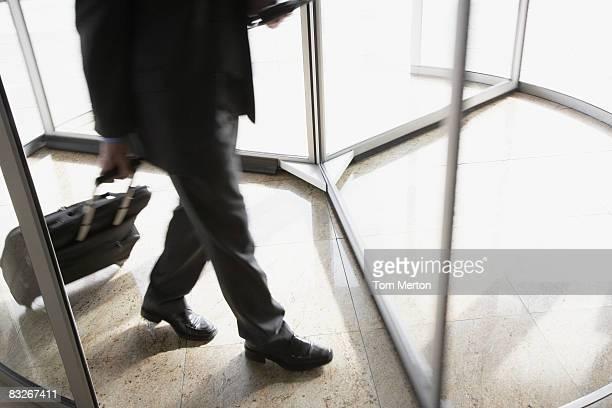 Businessman with suitcase using revolving door