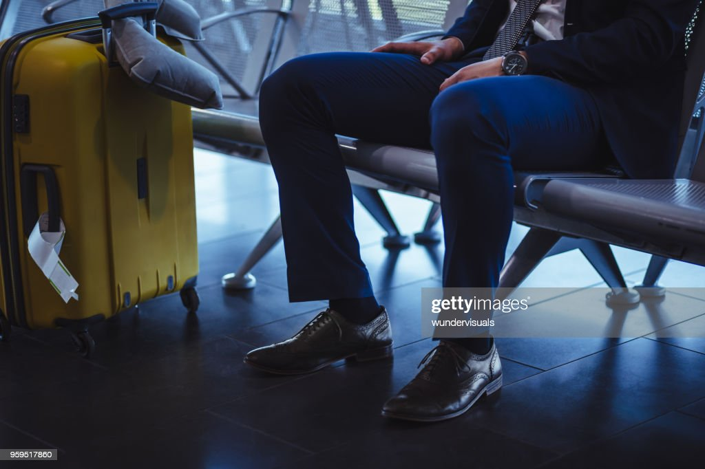 Geschäftsmann mit Koffer am Flughafen Abflughalle warten : Stock-Foto