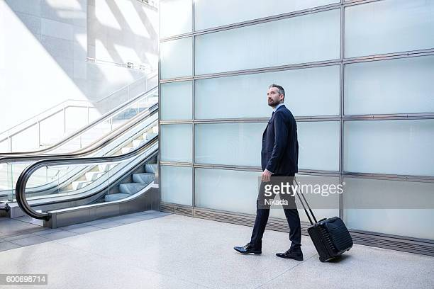 Businessman with suitcase walking by glass wall towards escalator