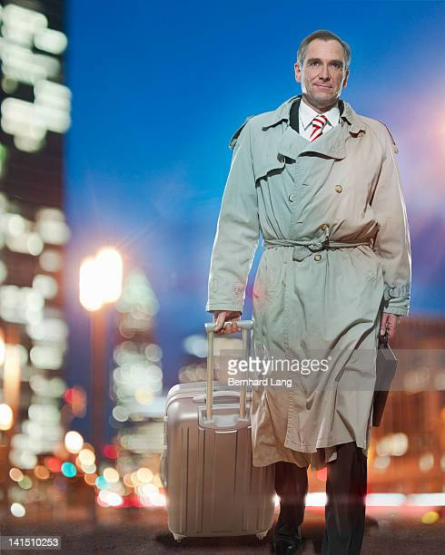 businessman with suitcase walking - long coat stock pictures, royalty-free photos & images