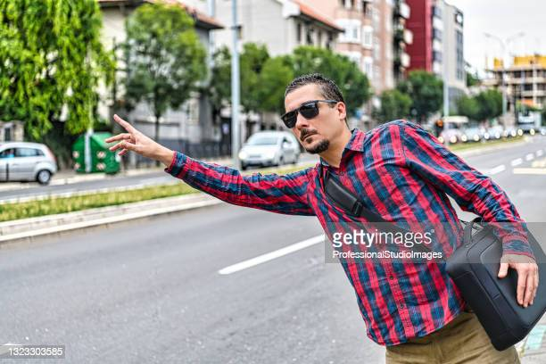 a businessman with sunglasses is standing in the street and waving with arm to catch a taxi. - world sports championship stock pictures, royalty-free photos & images