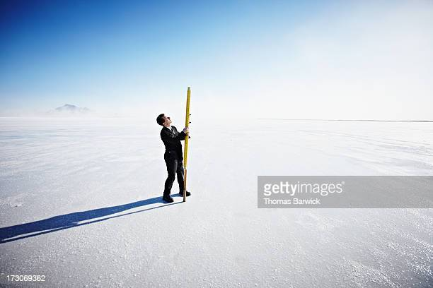 Businessman with surveyors stick on salt flats